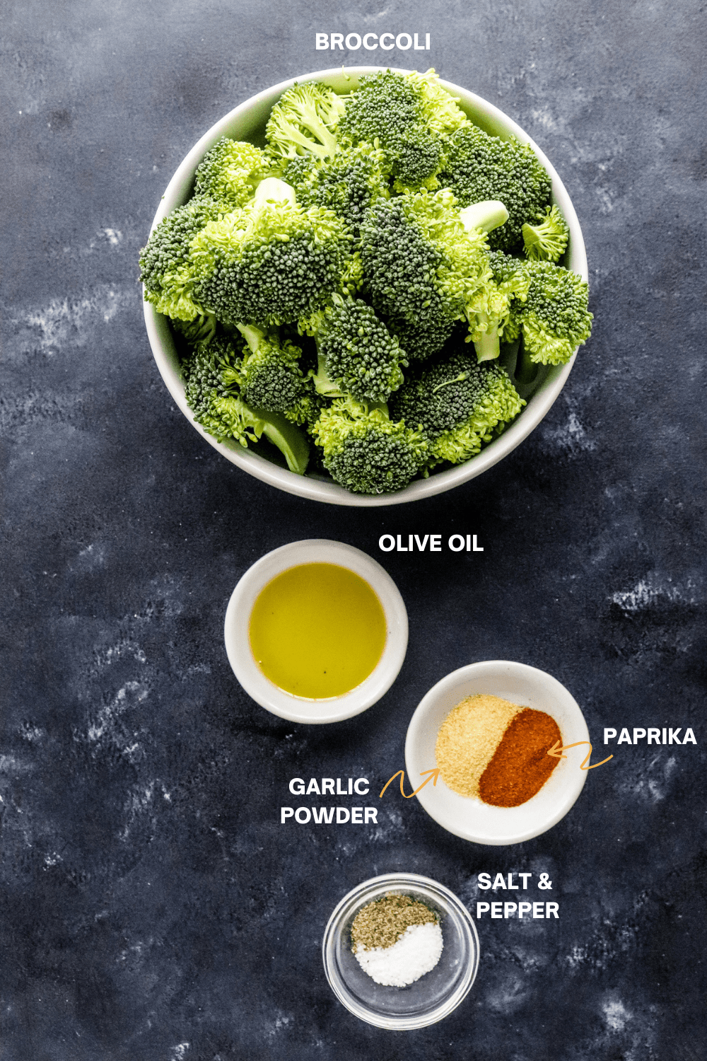 Broccoli cut up in a round white bowl with a small bowl of oil and spices next to it.