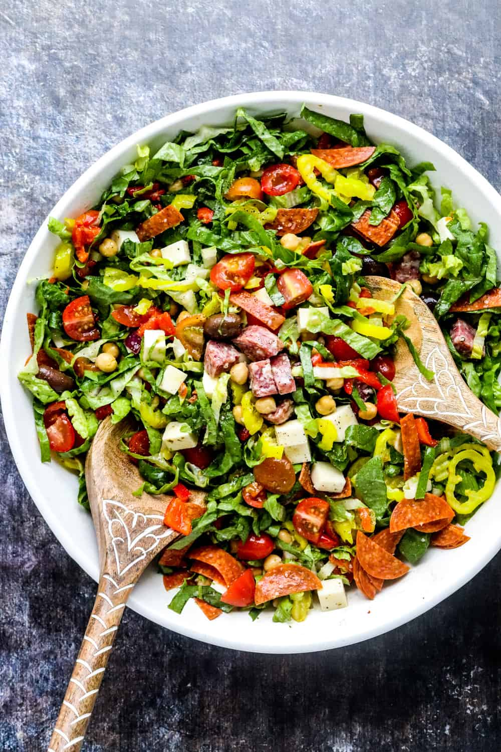 Large white bowl filled with chopped greens, tomatoes and chickpeas with two wooden spoons in it