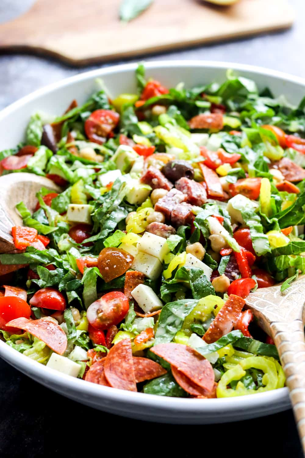 close up of chopped Italian salad in a white bowl with a wooden board behind it