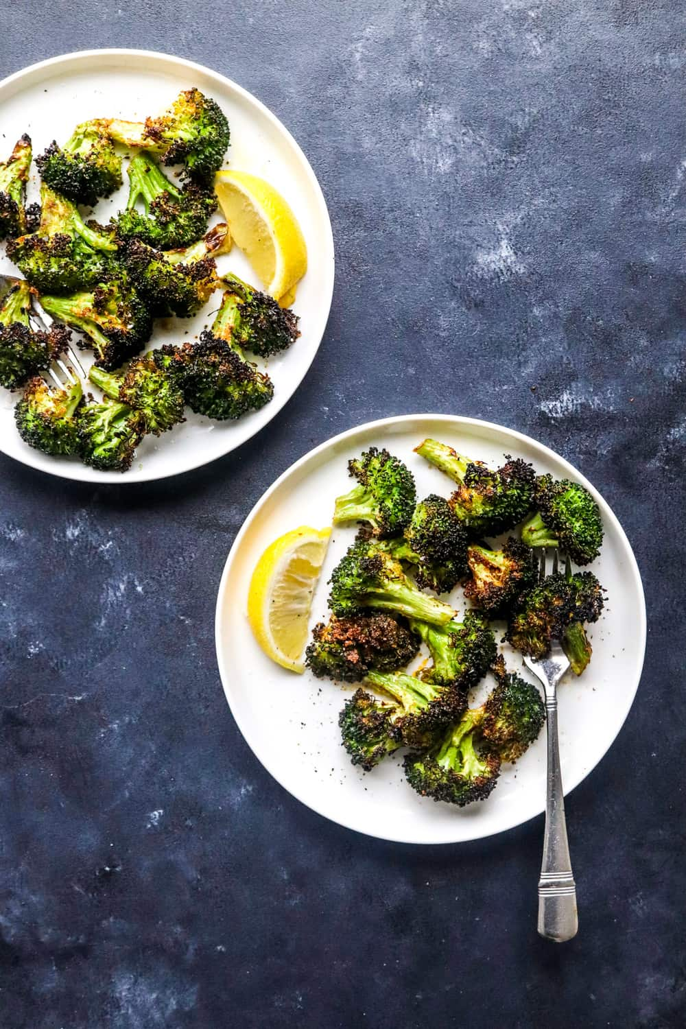 two round white plates with roasted broccoli on them with a lemon wedge next to it