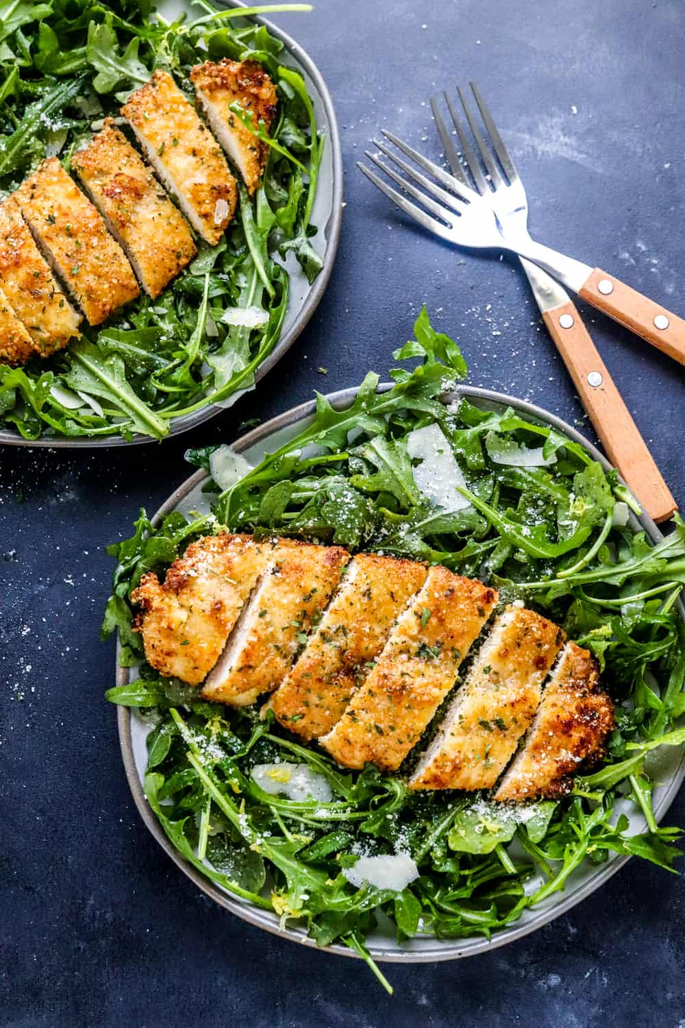 two grey plates filled with arugula salad topped with crispy breaded chicken breast