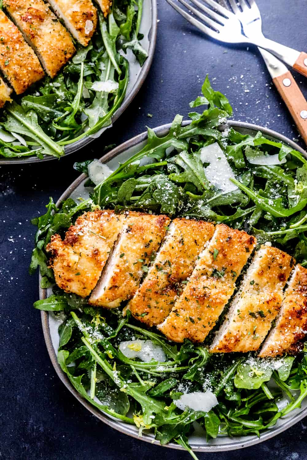 golden brown breaded chicken sliced into strips on a bed of arugula and shaved Parmesan