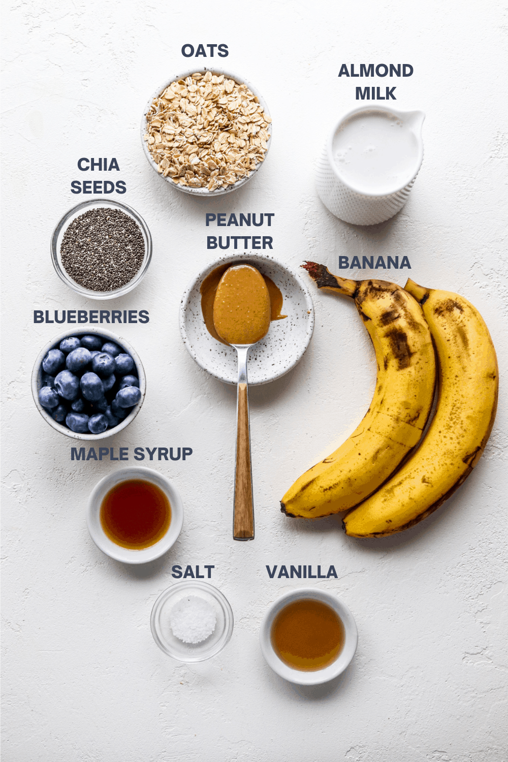 oats, milk, blueberries, peanut butter and whole bananas on a white surface