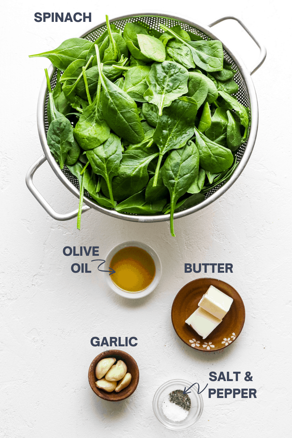 Spinach in a colander with olive oil, butter, salt and pepper in bowl next to it on a white surface