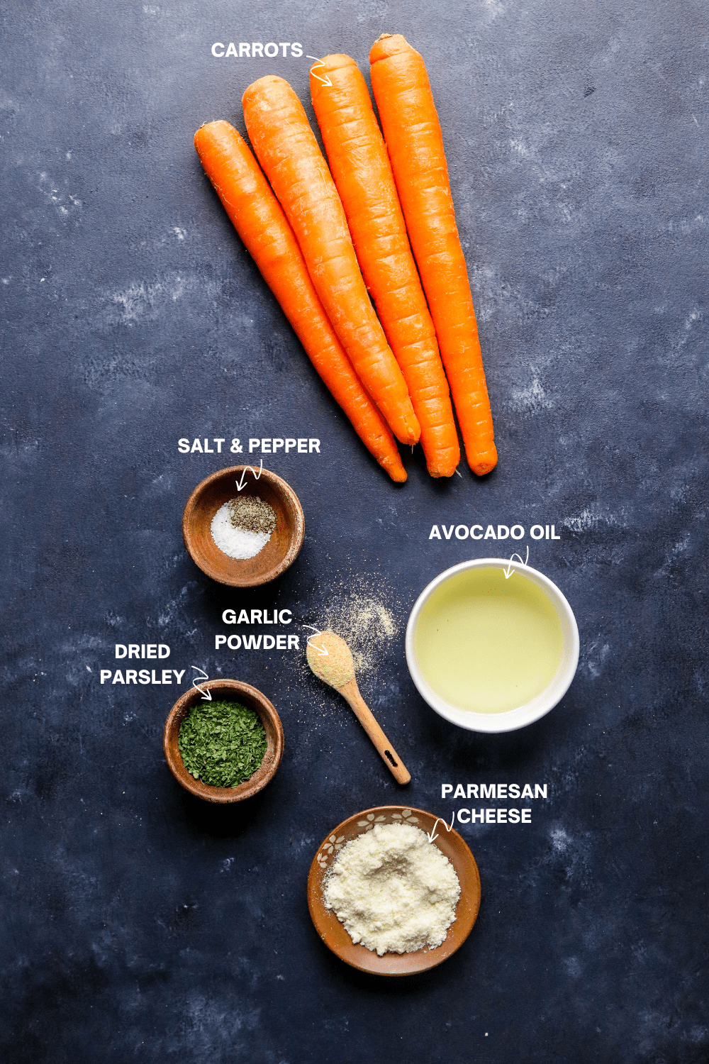 whole carrots, salt and pepper, avocado oil, parsley and cheese in small bowls on a blue surface with labels of each of the ingredients in white text.