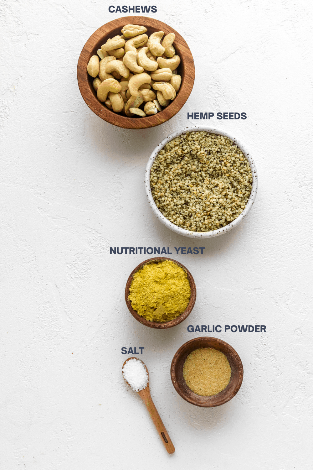 Bowl of cashews next to a round white bowl of hemp seeds with a wooden bowl of nutritional yeast and bowl of garlic powder in front of it.
