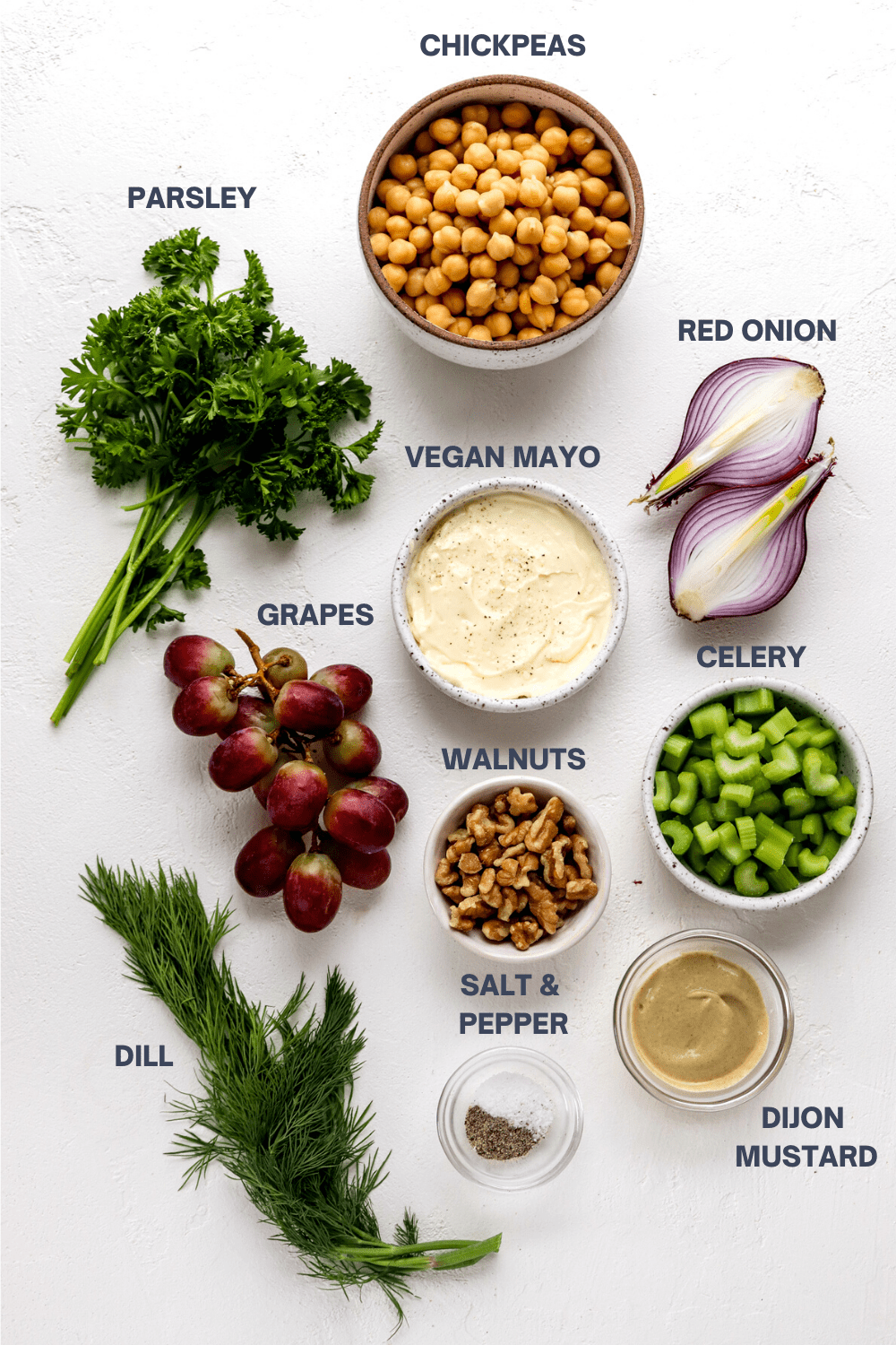 Bowl pf chickpeas, chopped celery, diced grapes, walnuts, mayo, mustard and fresh herbs on a white surface.