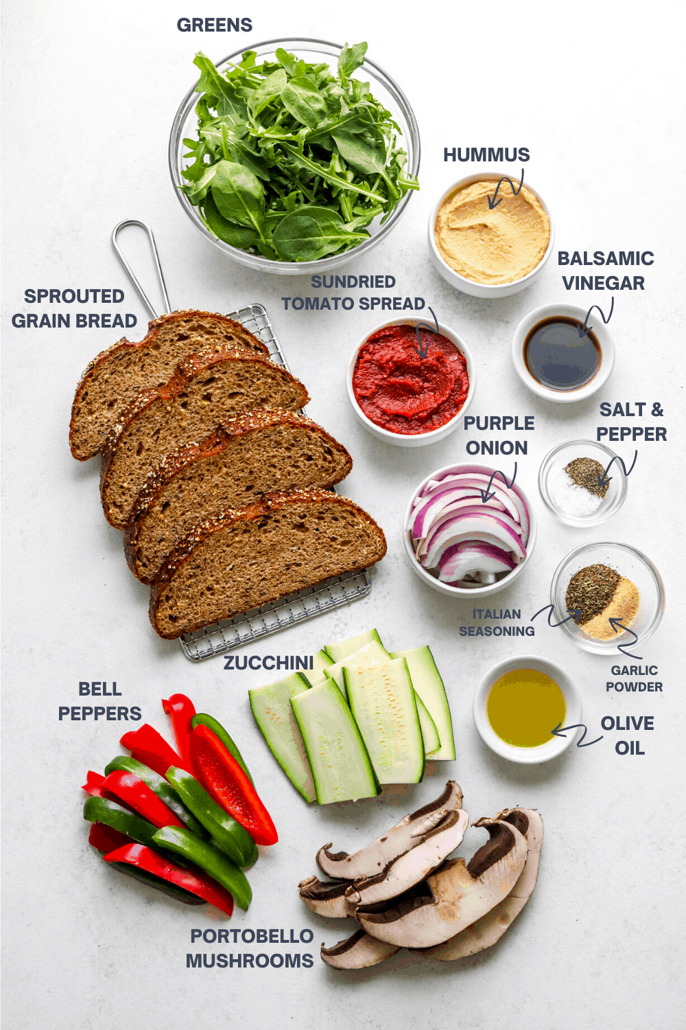 Whole grain bread sliced, sliced zucchini, peppers, onions and mushrooms on a white surface with olive oil and spices next to it.