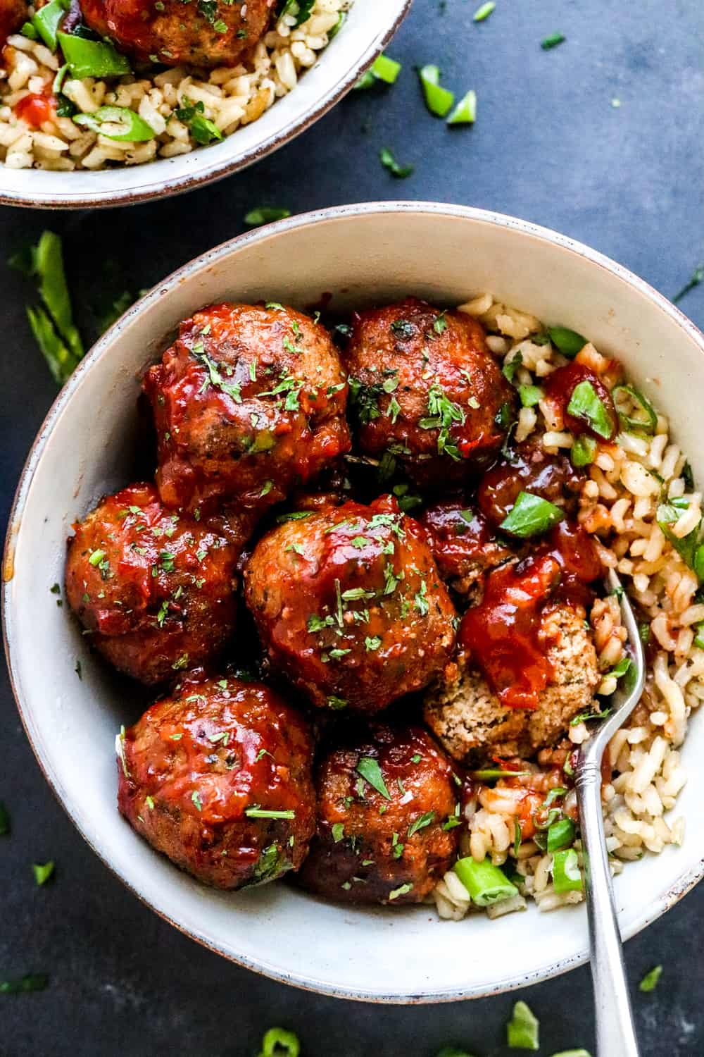 close up of round healthy turkey meatballs covered in chili sauce over cooked brown rice with a fork cutting into one of the meatballs