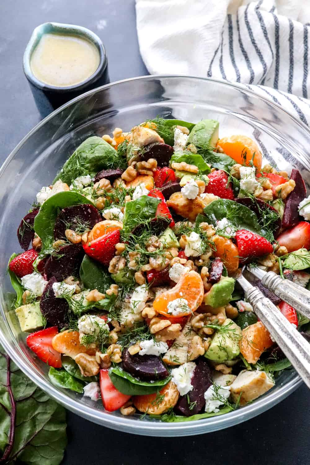 Round bowl filled with veggies and fruits topped with chicken and soft cheese and herbs with a metal serving spoon sticking out of the bowl.