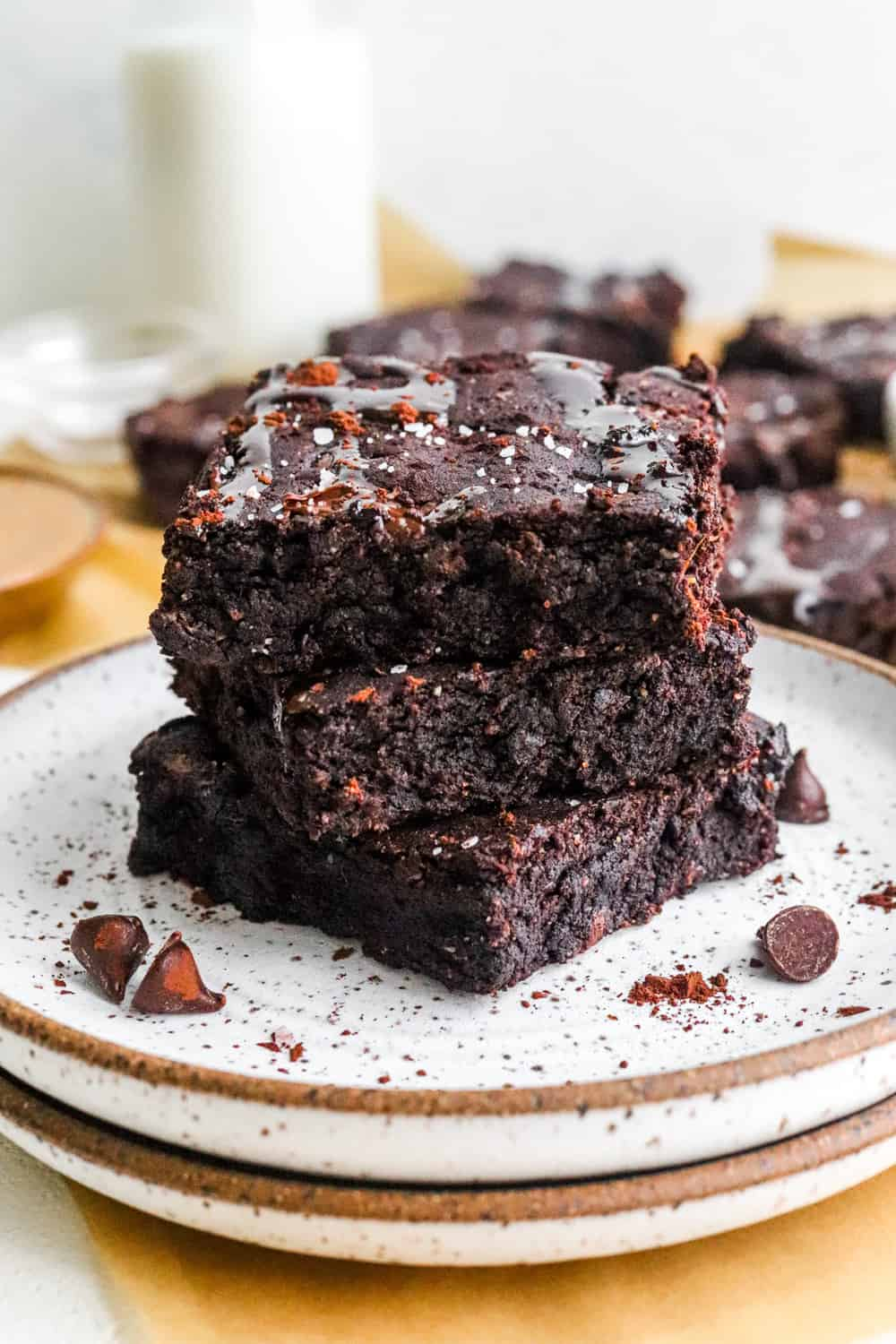 stack of fudgy brownies on a specked white plate with more brownies behind it.