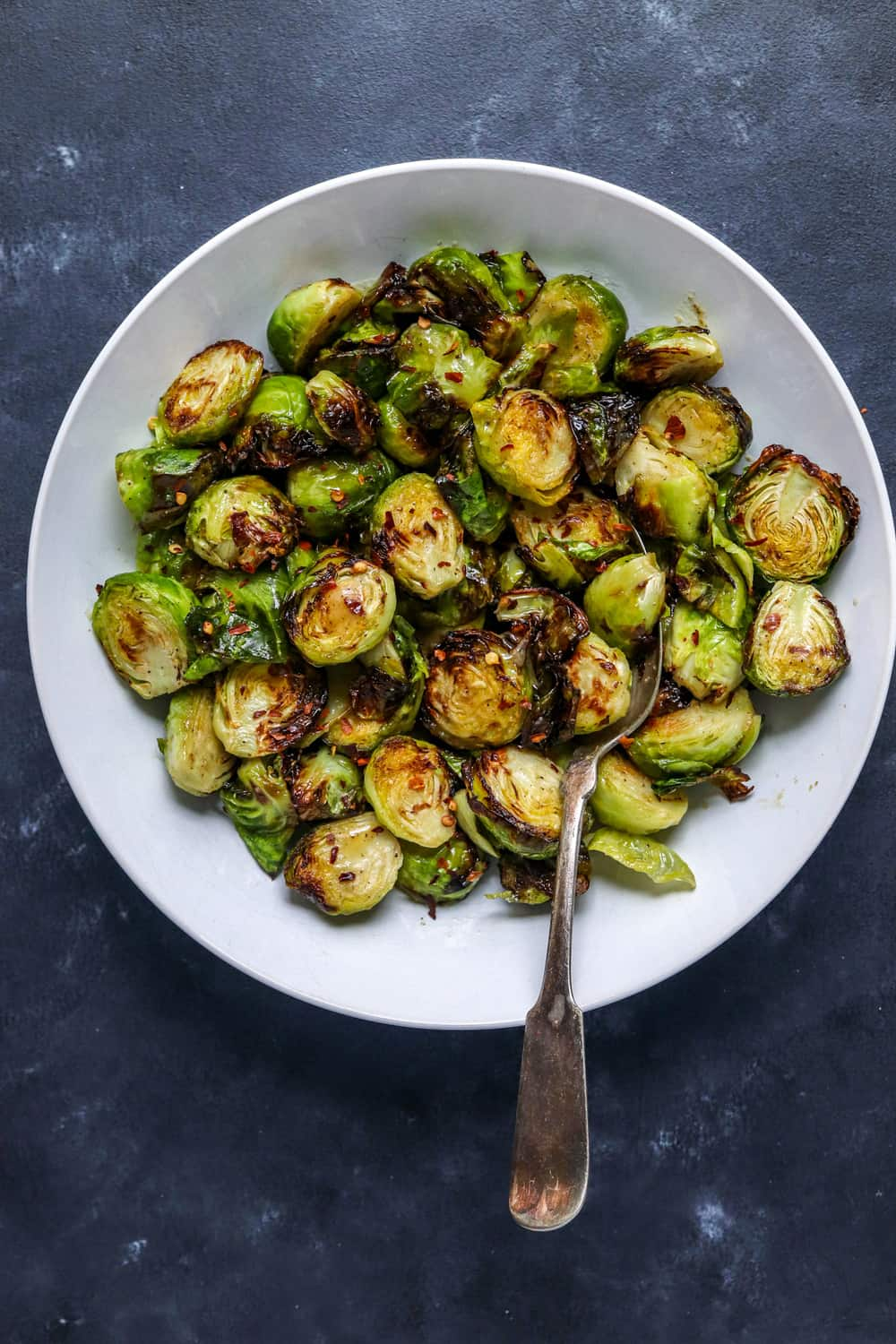 Round white bowl filled with crispy roasted air fryer Brussel sprouts with a spoon in them.