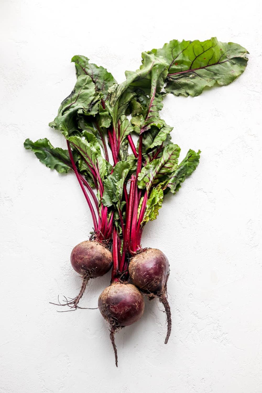 Bunch of whole beets with beet greens attached on a white surface.