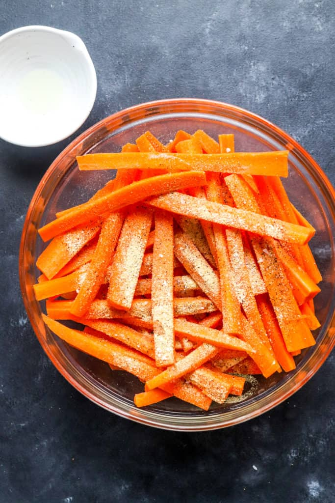 Carrot fries in a large round glass bowl with garlic salt and pepper on them with a small white bowl of oil behind it.