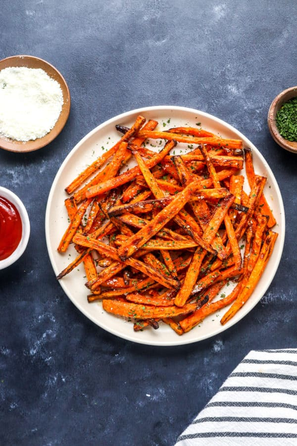 Round beige plate with a pile of golden brown carrot fries on it topped with herbs and shredded parmesan cheese with a small bowl of ketchup next to it