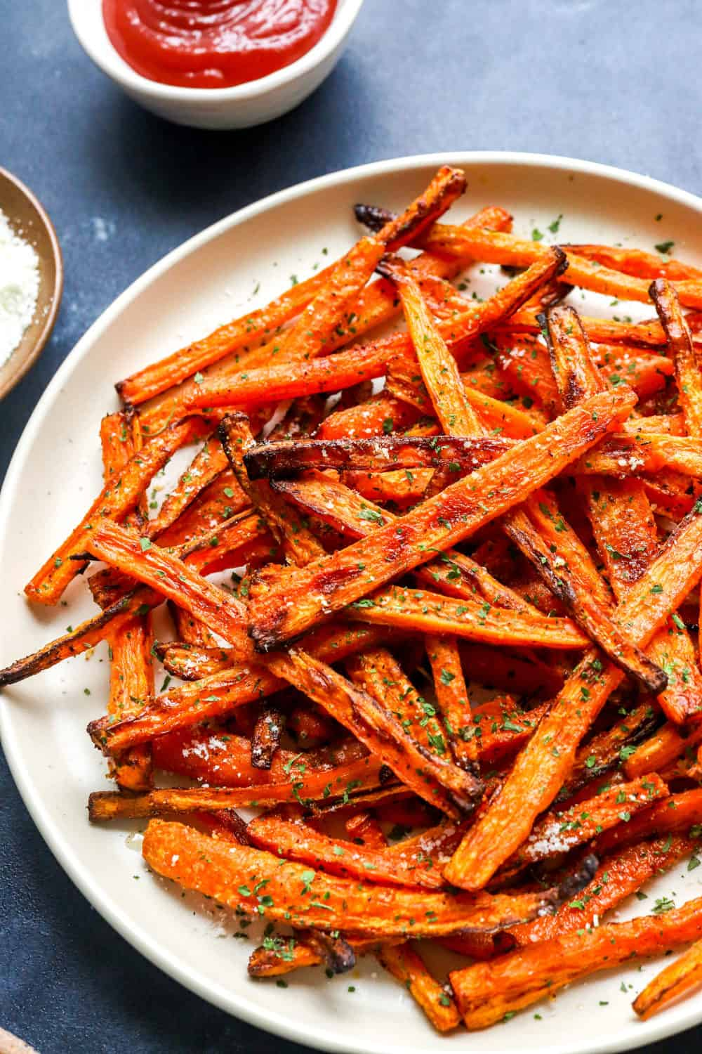 carrot sticks that have been cooked on plate in a criss cross pattern with shredded parsley on them and ketchup in a bowl behind them.