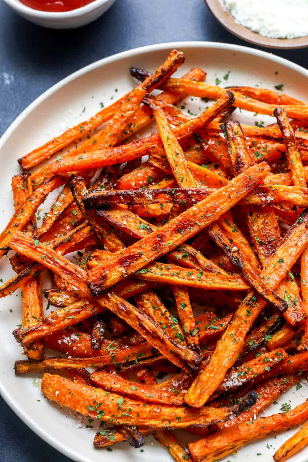 Bright orange golden brown carrot sticks in a pile on a plate topped with dried parsley and grated parmesan cheese.
