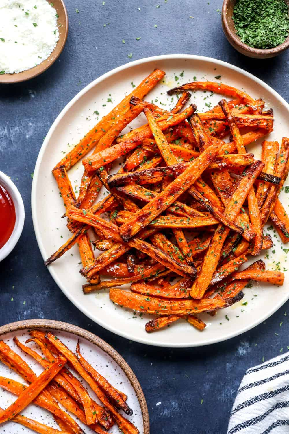 pile of crispy carrot fries on a white round plate with more in front of it and a bowl of ketchup next to it