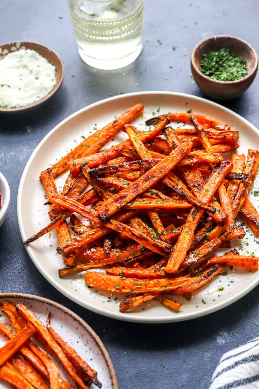 crispy fried carrots on a round plate with shredded parmesan cheese in a bowl next to it and a glass of wine in back of it.