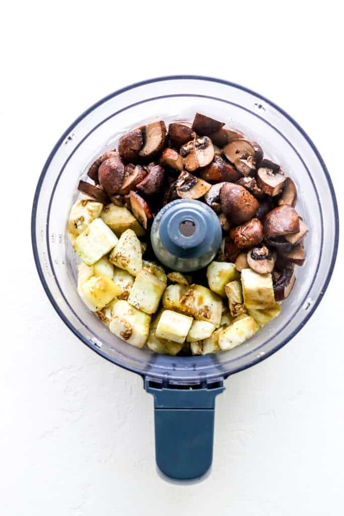 Roasted diced eggplant and sliced mushrooms in the bowl of a food processor