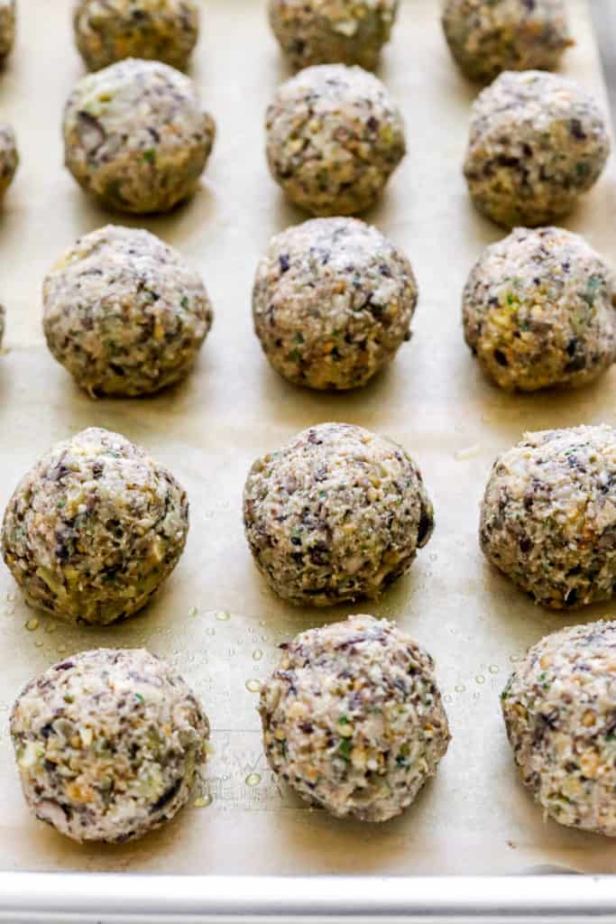 Eggplant meatball mixture rolled into even size balls on brown parchment paper