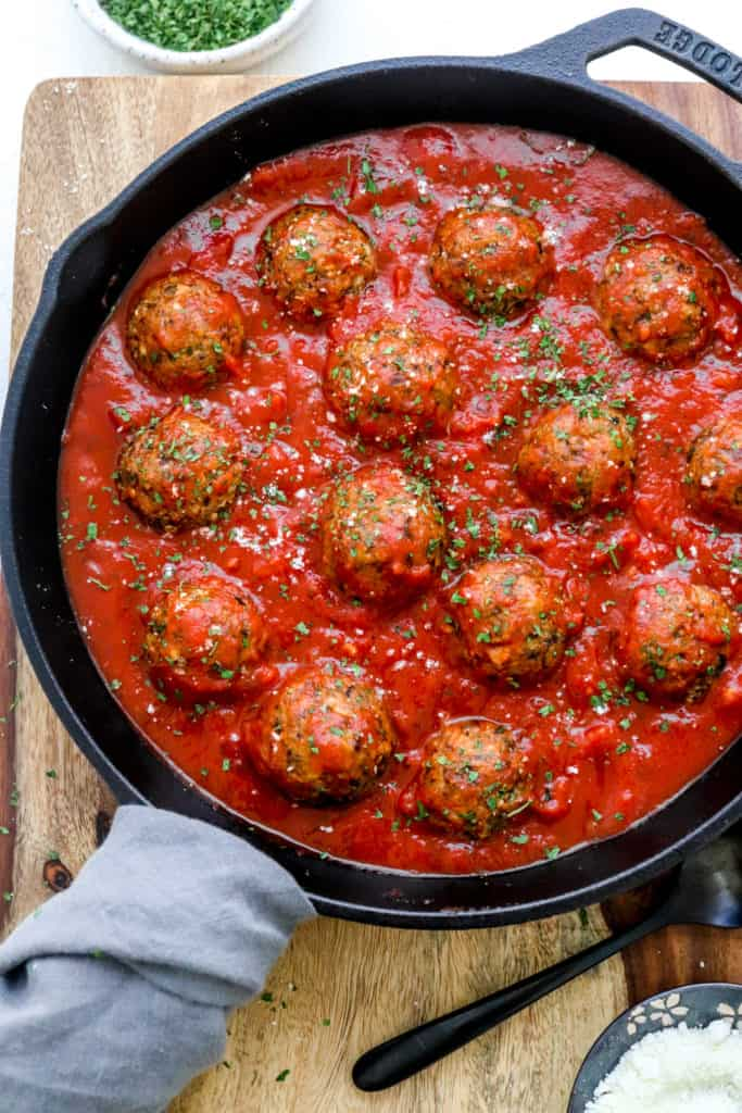 metaballs in red sauce in a round black cast iron pan with a grey towel wrapped around the handle of the pan