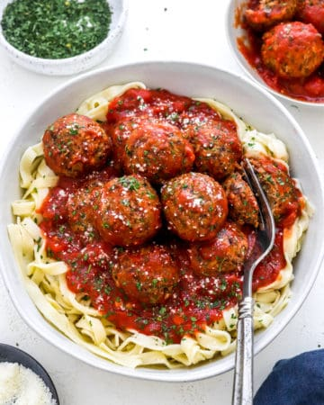 Bowl of linguine topped with meatballs covered in red sauce topped with parsley with a fork cutting into one of the meatballs
