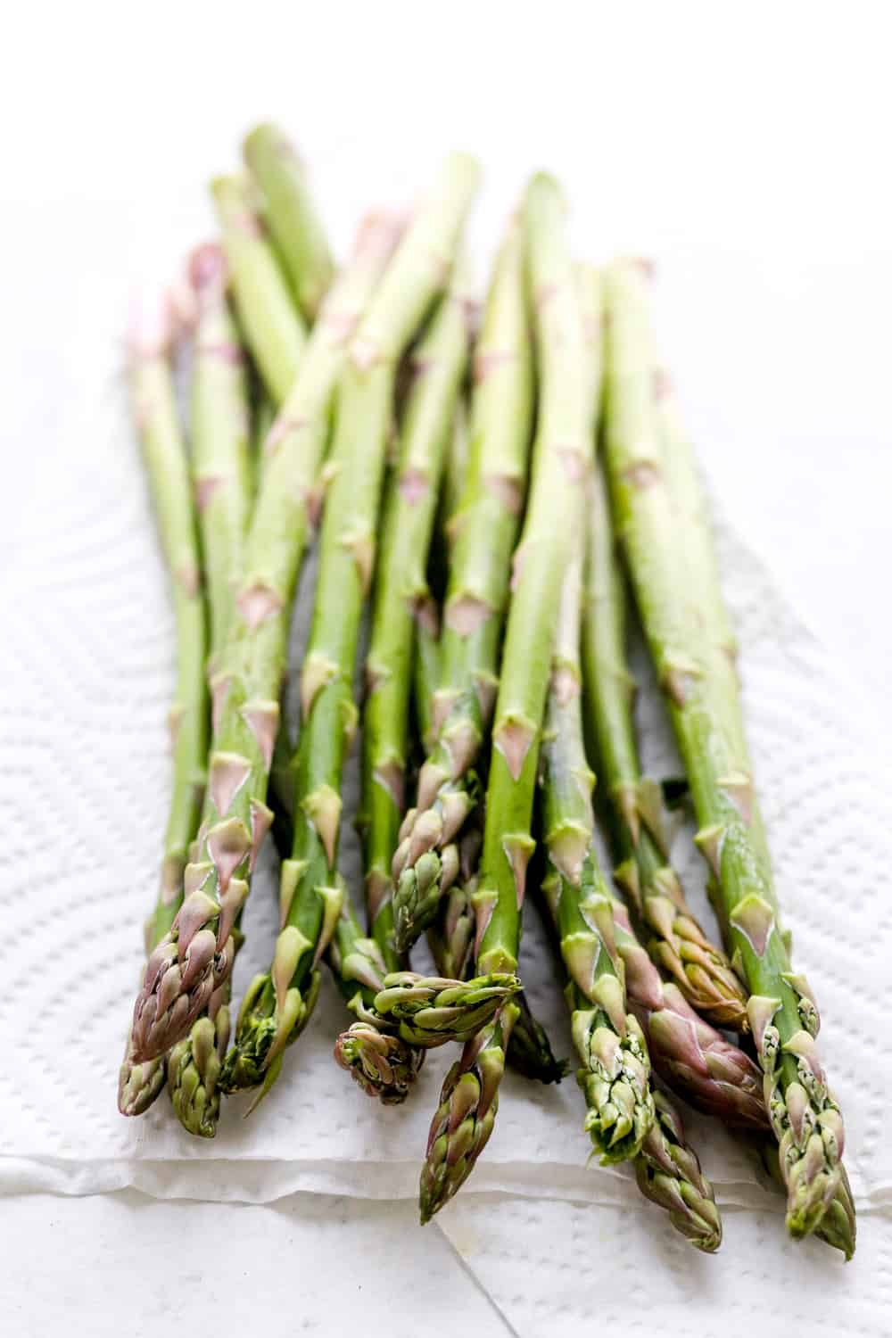 A bunch of green asparagus in a pile on top of a folded white paper towel.