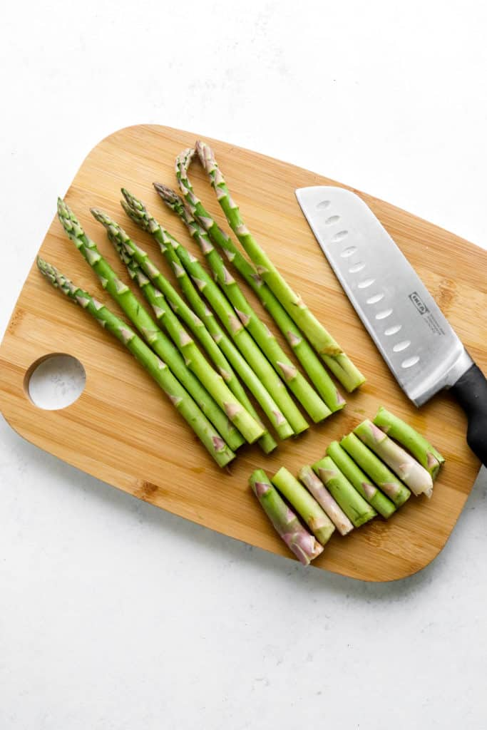 Asparagus spears on a wooden cutting board with the ends sliced off and a knife next to it