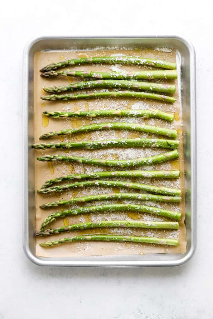 Green asparagus in a single layer on a baking sheet on top of brown parchment paper with parmesan and oil on it