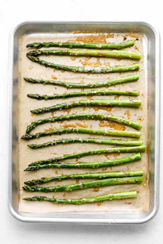 Crispy roasted parmesan asparagus spread out on a baking sheet with shredded parmesan sprinkled on top of it