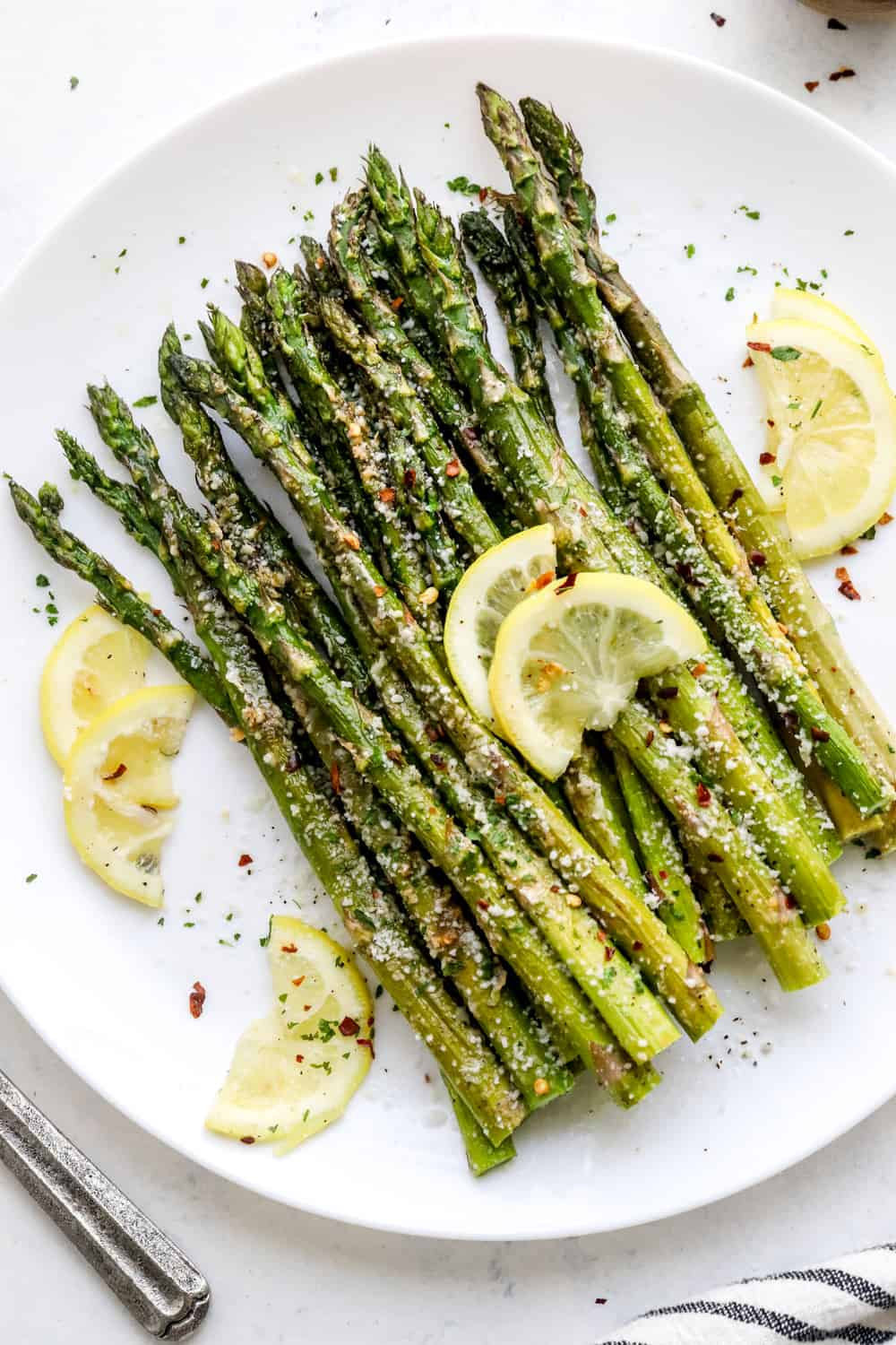 Cooked asparagus in a pile on a round white plate with sliced lemon laying on top of it