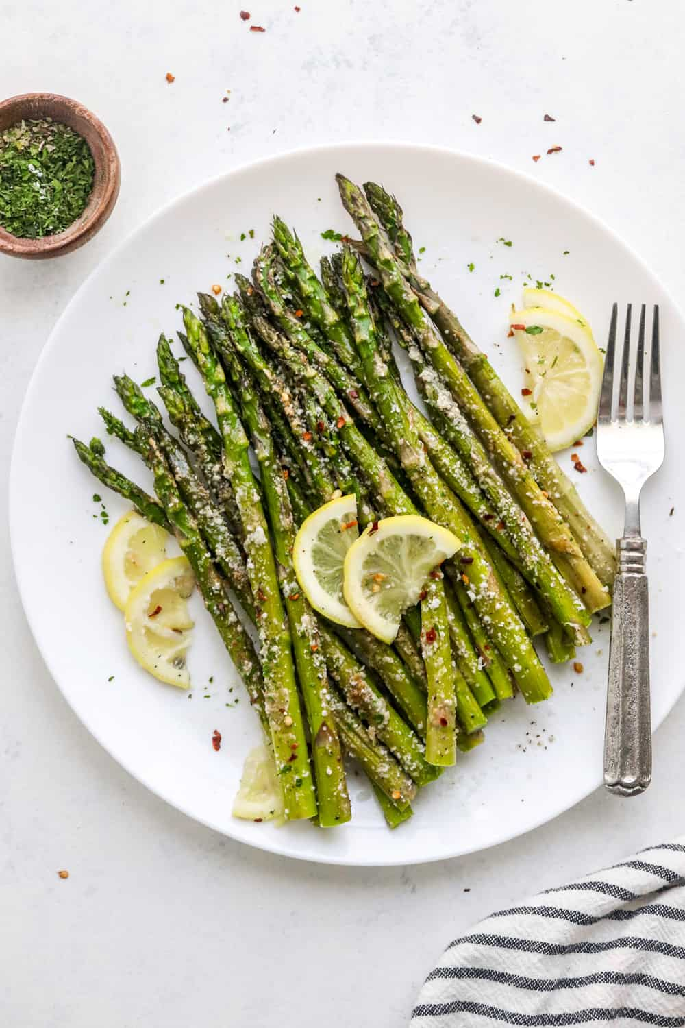 Roasted asparagus with parmesan piled up on a round white plate with sliced lemon in it and a silver fork next to it.