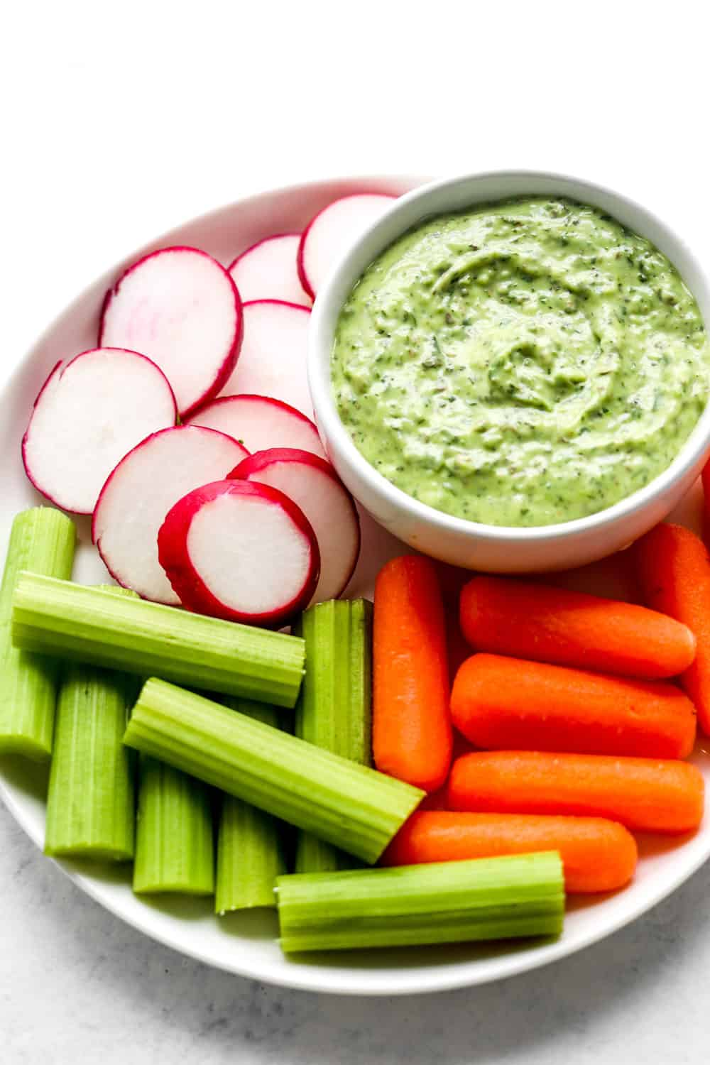 Green goddess dressing in a dip bowl on a round white plate with carrots, radishes and celery sticks around it.