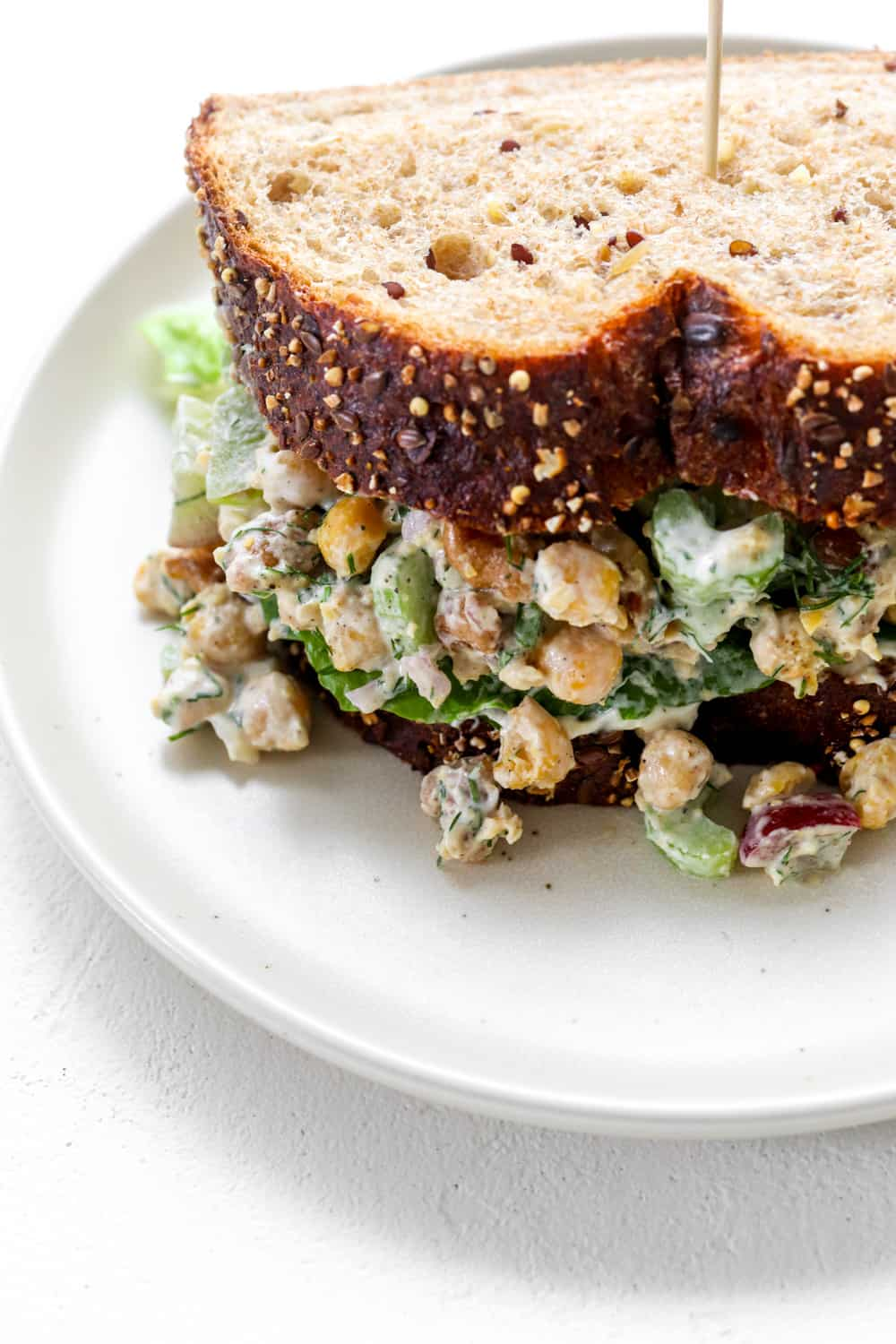 Chickpea chicken salad between two thick slices of whole grain bread on a round white plate