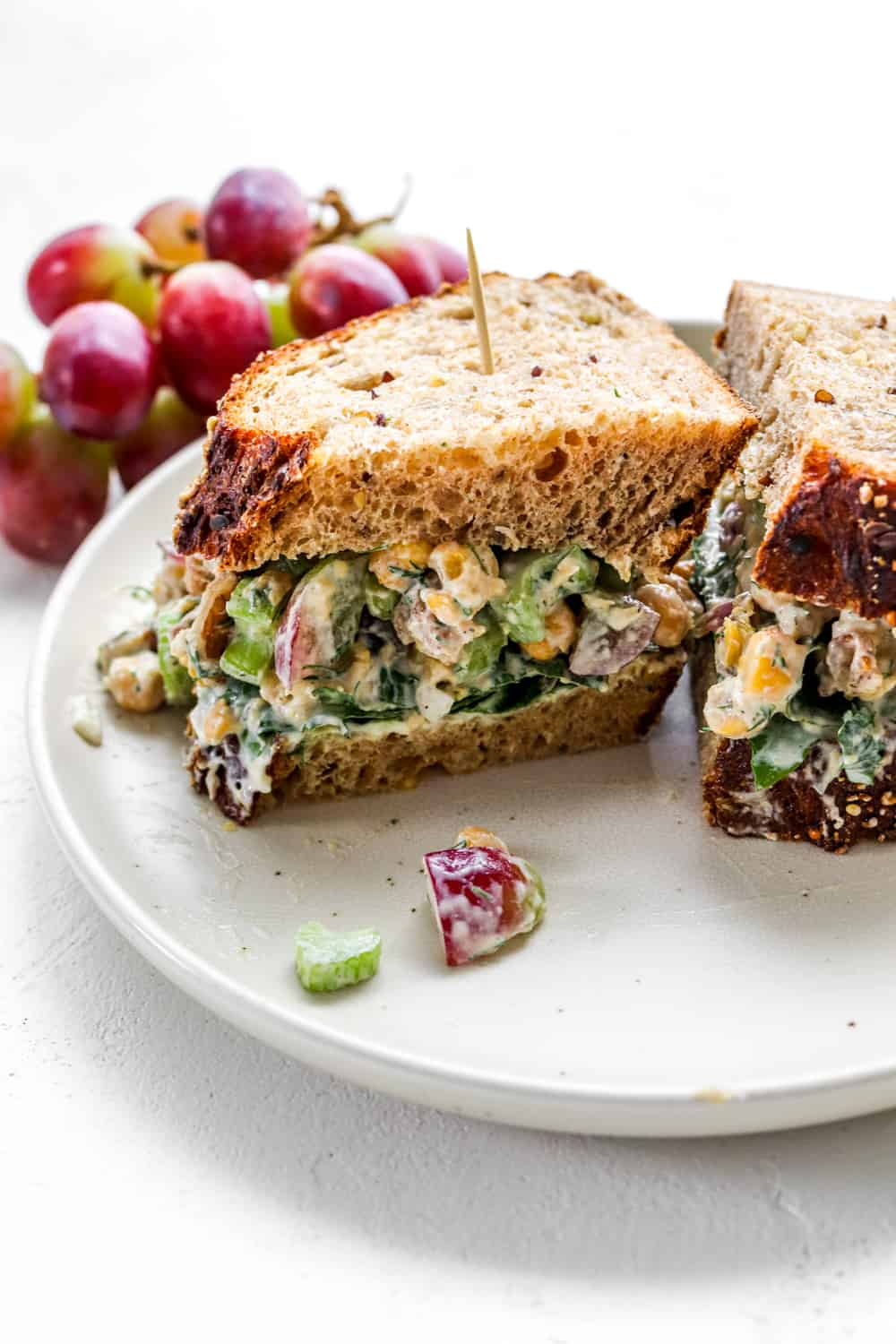 creamy salad in between whole wheat slices of bread on a plate