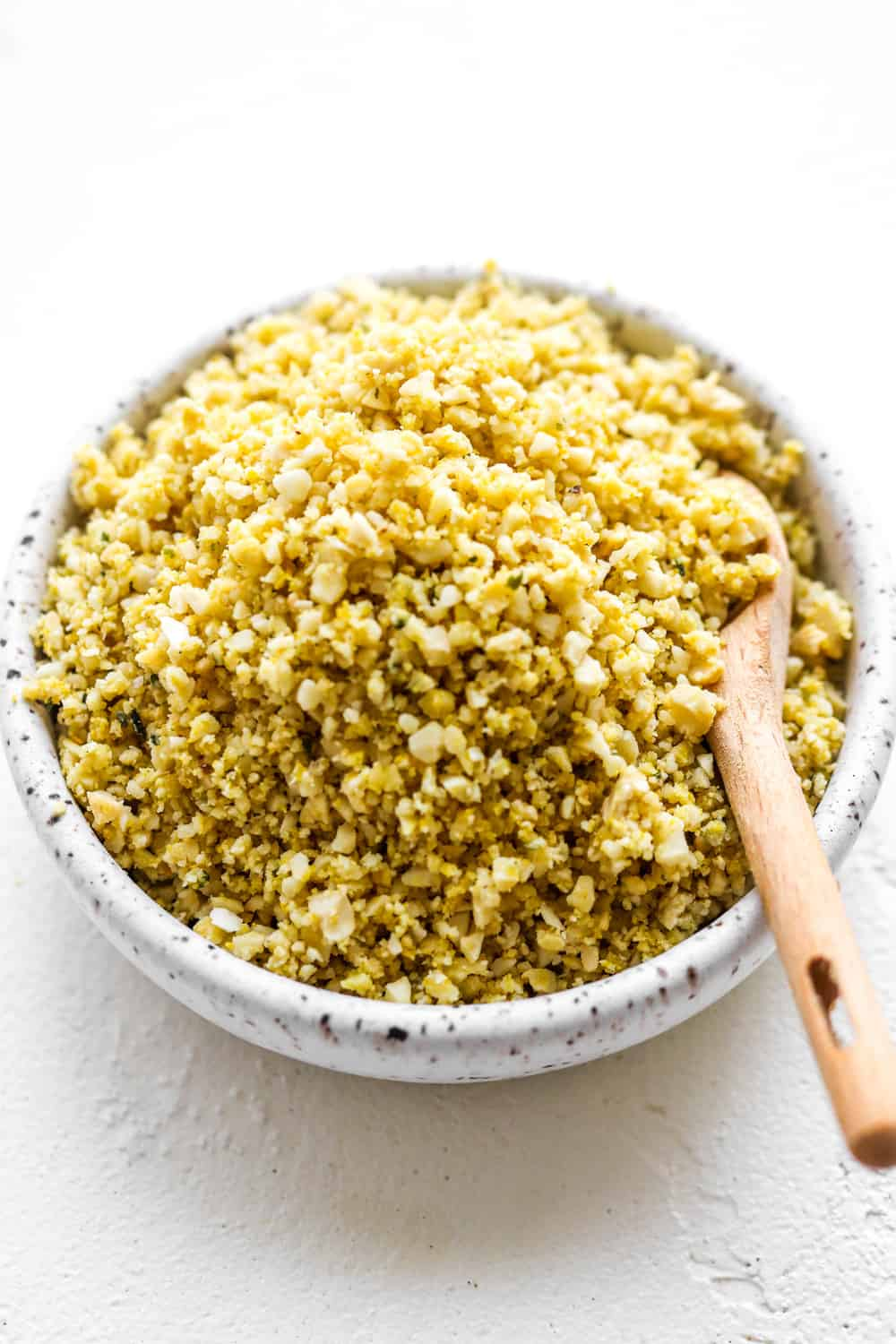Round white specked bowl filled with nut and seed parmesan cheese with a small wooded spoon in it.
