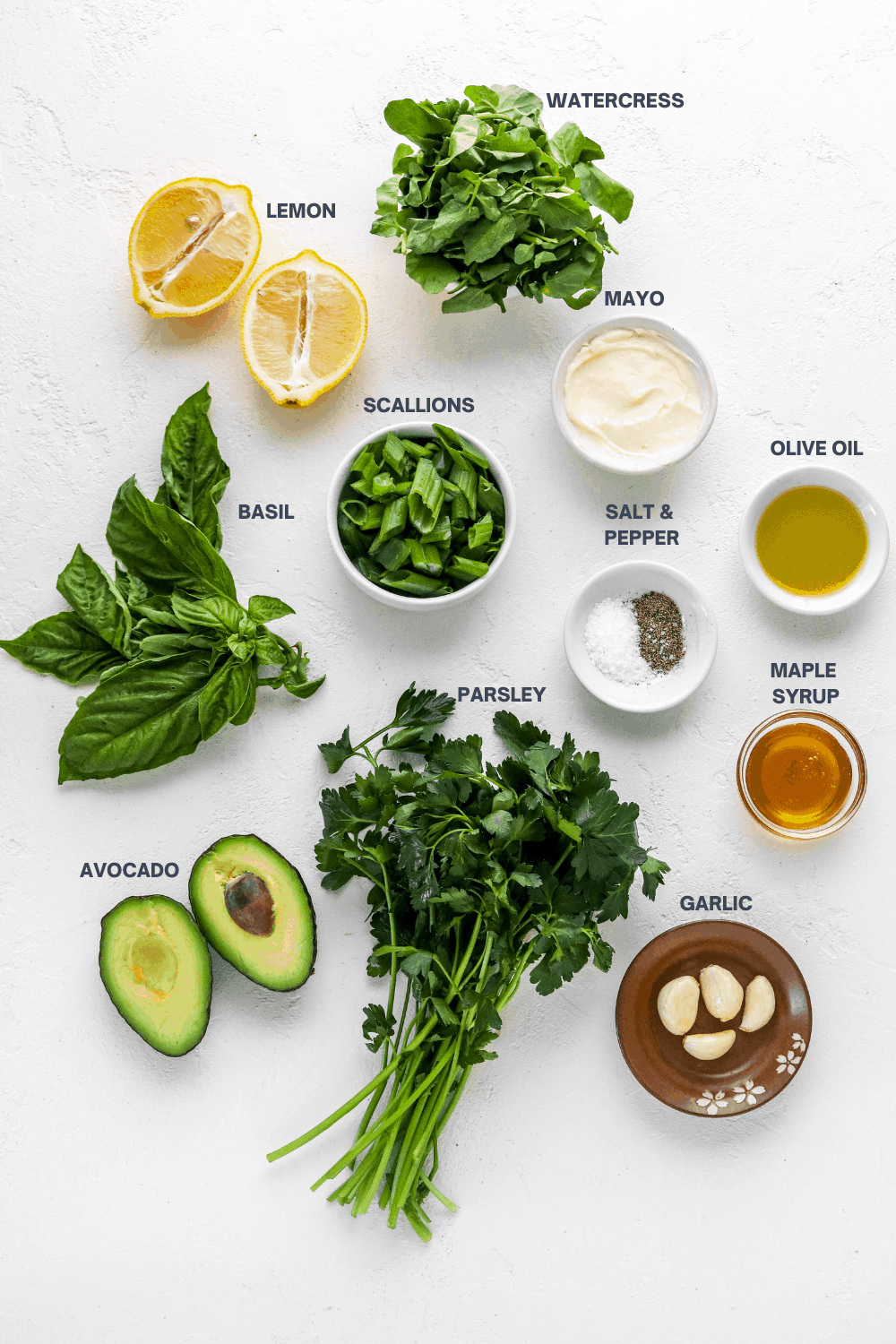 parsley, basil, lemon sliced, mayo, salt and pepper, sliced avocado, garlic and olive oil in bowls on a white surface