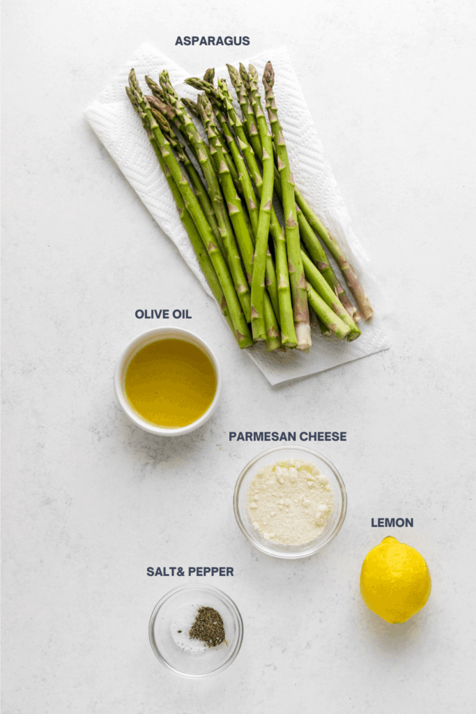 Raw asparagus, olive oil in a white bowl, shredded parmesan cheese, lemon, salt and pepper on a white surface with labels above them.