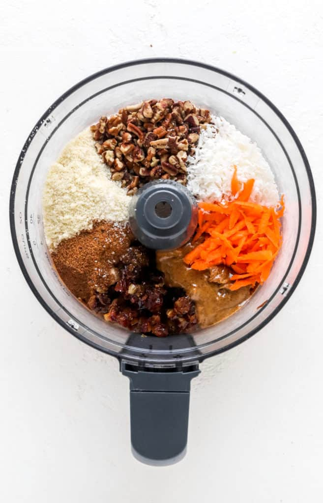 Shredded carrots, coconut, pecans, dates and almond butter separated in the bowl of a food processor
