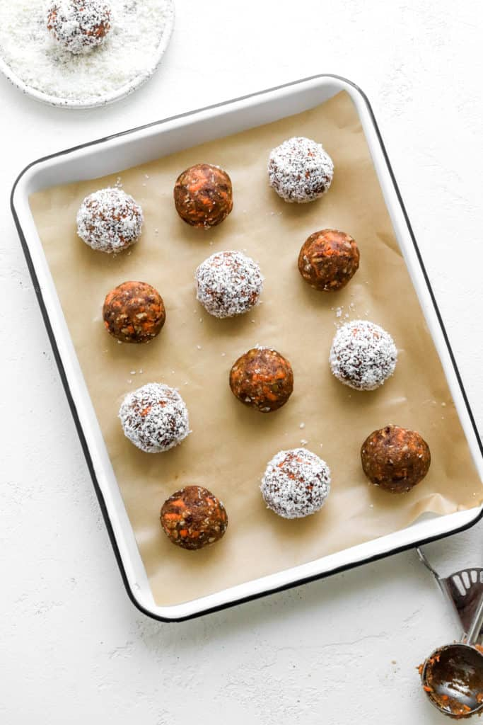 Rolled dessert balls on a baking sheet with some rolled in shredded coconut on top of brown parchment paper on a white pan