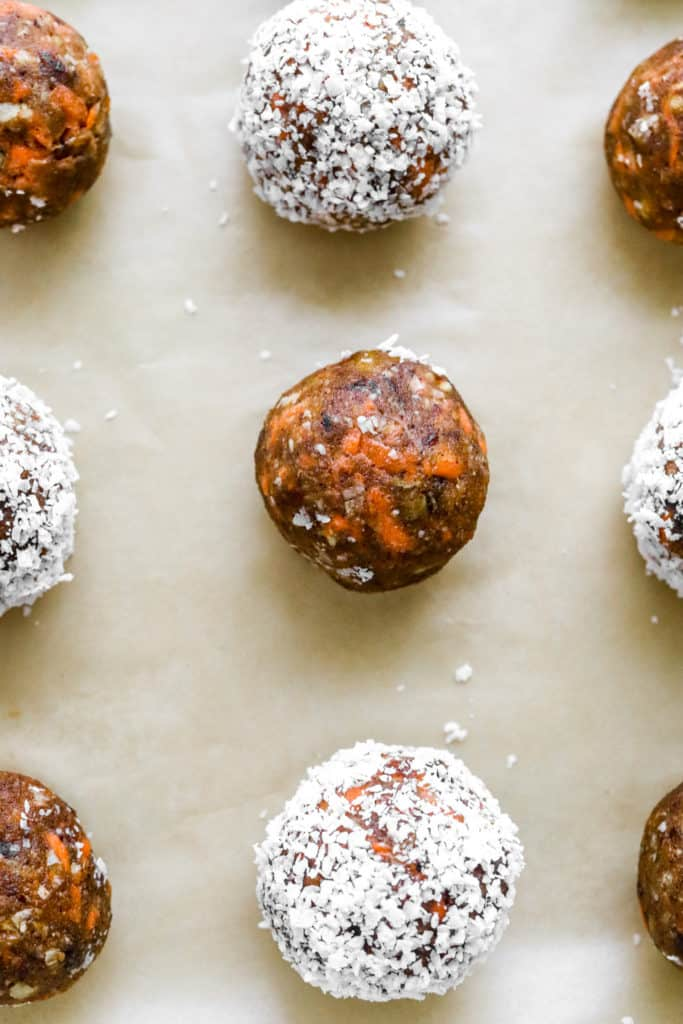 brown energy ball with carrots in ti and some more around it rolled in shredded coconut