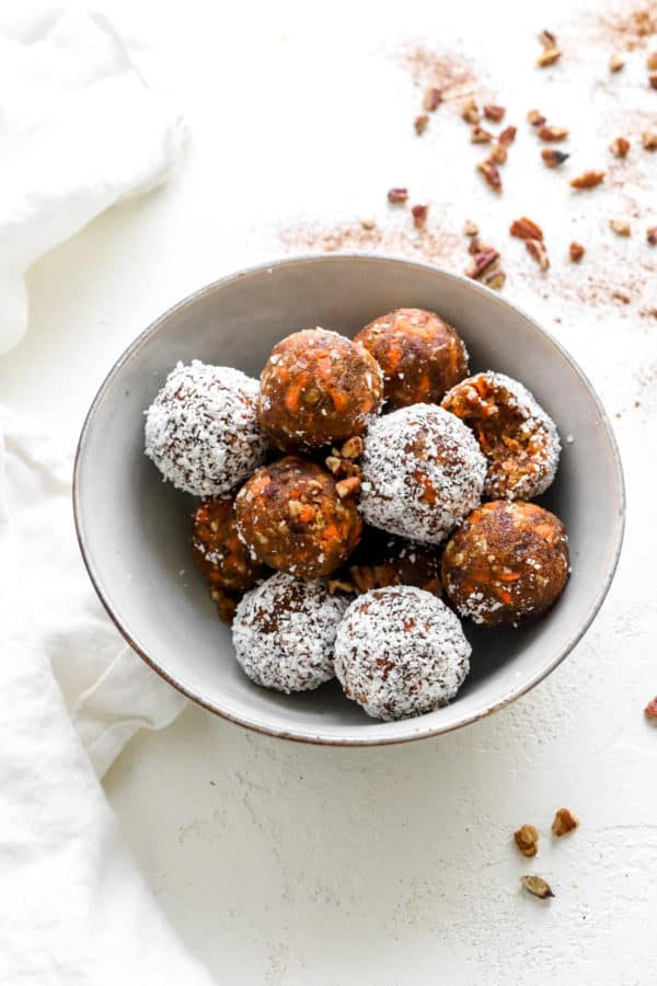 Round gray bowl on a white surface filled with dessert balls with some white and some brown