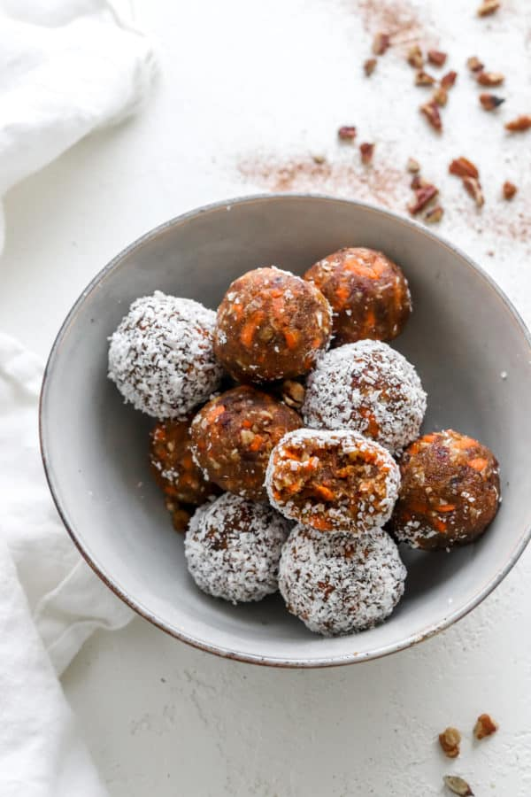 Round gray bowl filled with brown and white carrot cake balls with with chopped nuts behind it and a white linen next to the bowl.