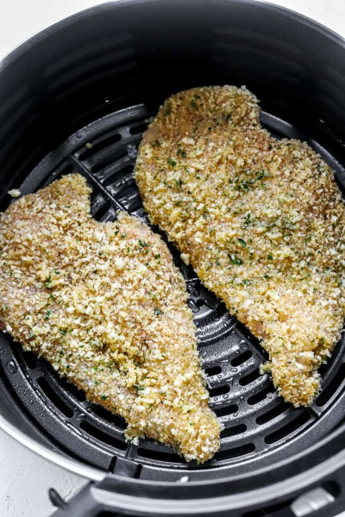 raw breaded chicken cutlets in the basket of an air fryer