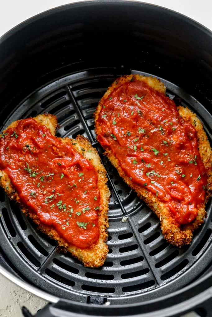 two cooked breaded chicken cutlets topped with red sauce in an air fryer basket next to each other