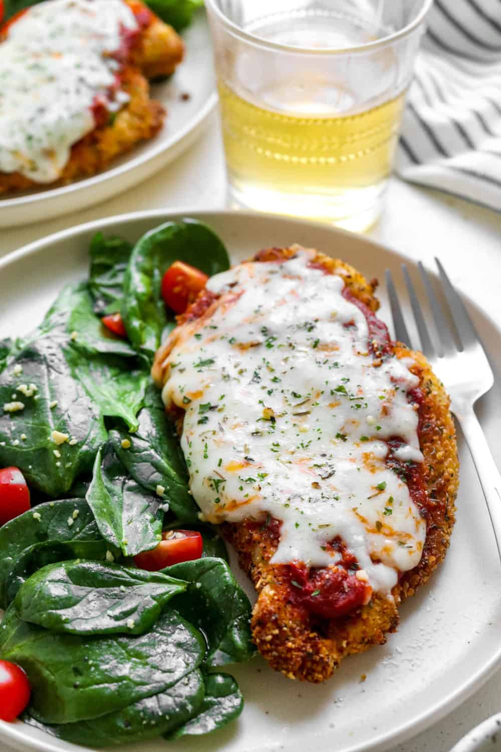 Crispy breaded chicken parmesan on a plate with spinach salad with a form next to the plate and a glass of white wine behind it