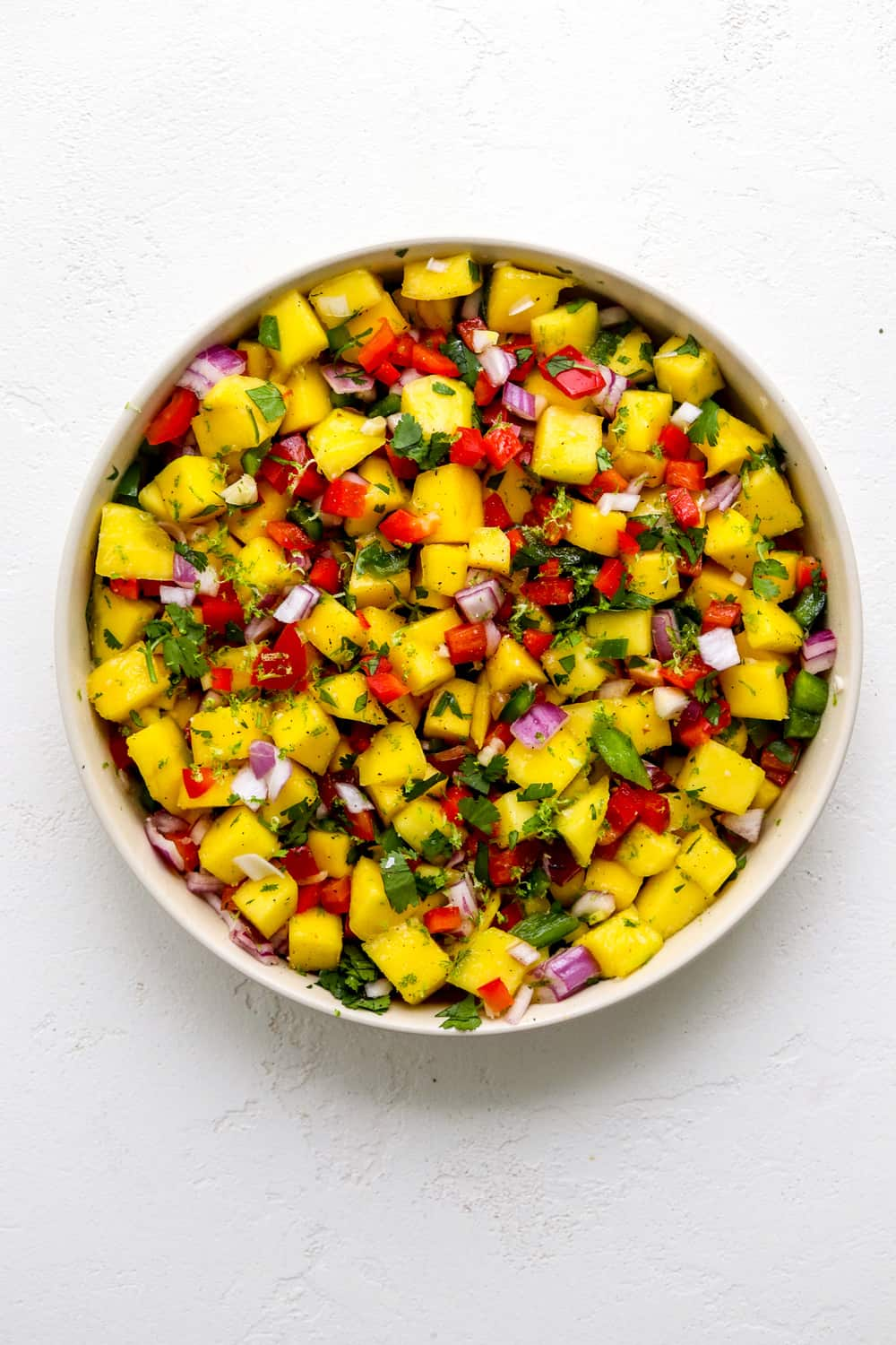 Single round bowl of spicy mango salad with red and green peppers and herbs in it on a white surface