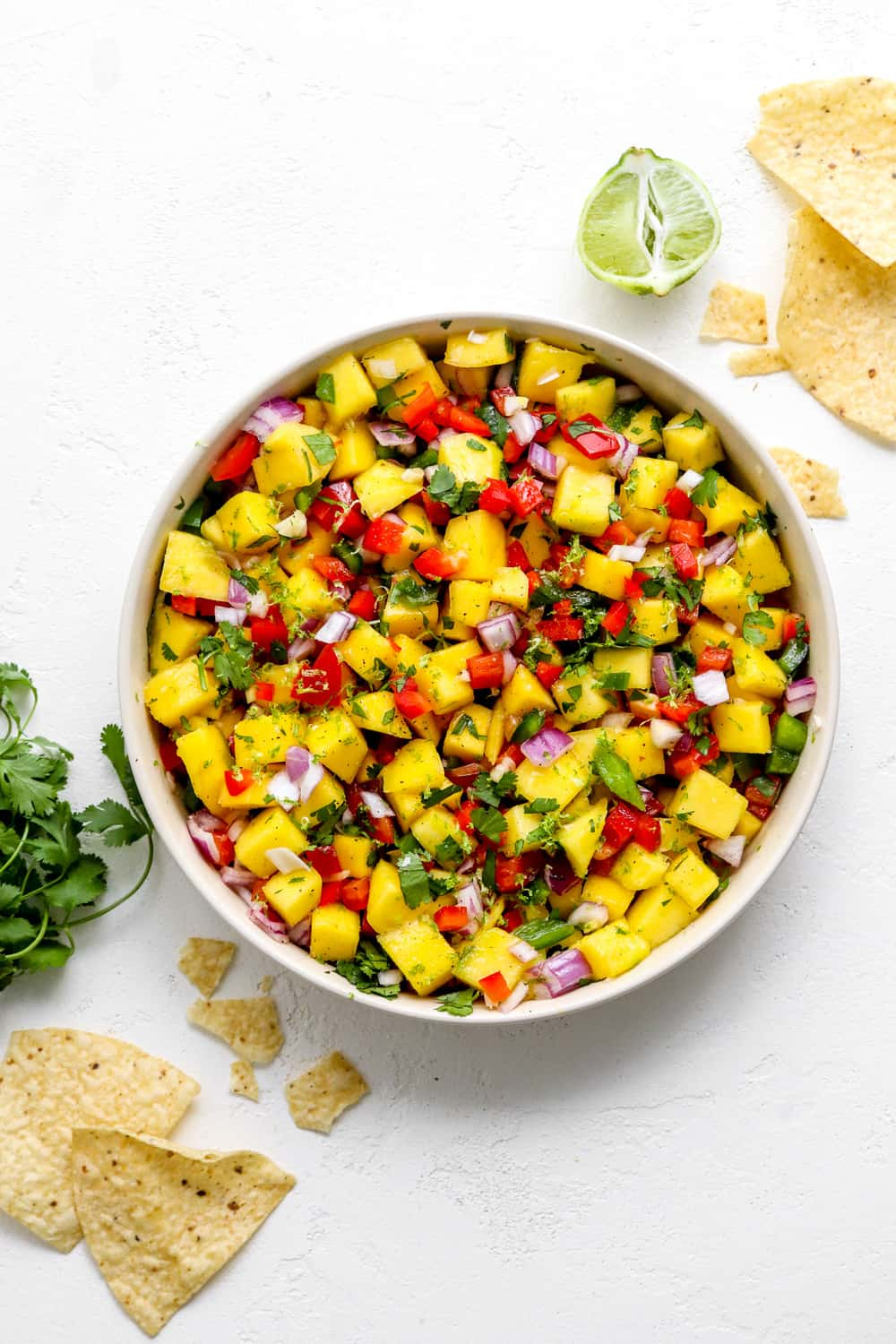 Bowl of yellow and red salsa with mangoes and peppers in it with whit corn tortilla chips next to it and a lime behind it.