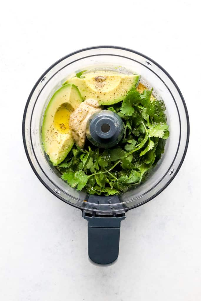 Cilantro, sliced avocado, mustard and olive oil in the bowl of a food processor